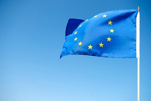 Ondeando la bandera de la unión europea sobre el fondo azul.