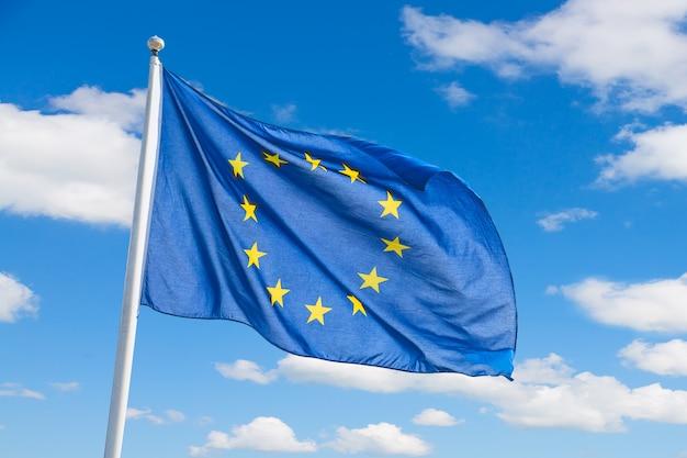 Ondeando la bandera de la unión europea sobre fondo de cielo azul.