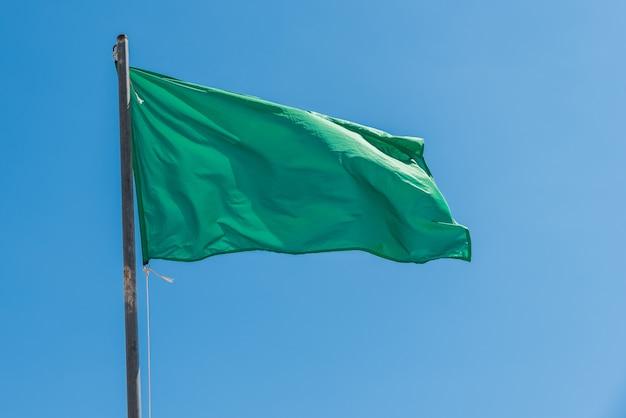 Ondeando la bandera verde que indica la tranquilidad del mar