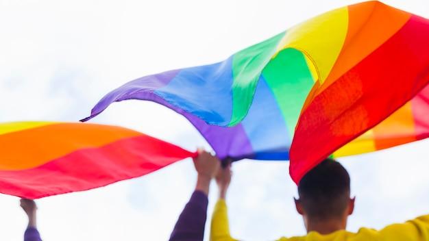 Ondeando banderas de arcoiris sostenidas por gays en desfile