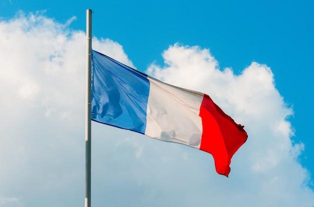 Ondeando la colorida bandera de francia en el cielo azul.