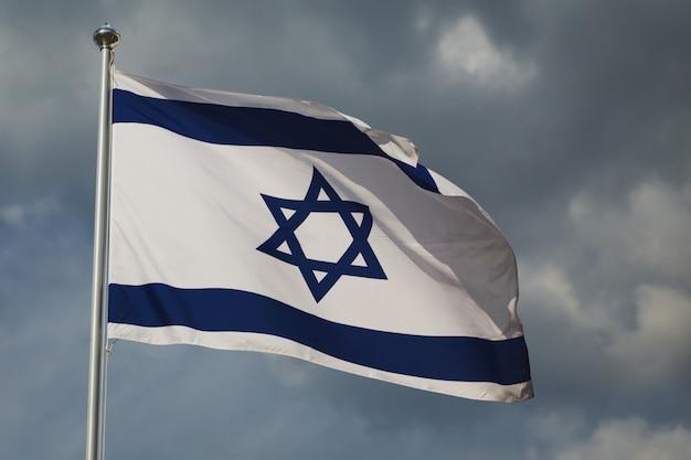 Ondeando la colorida bandera de israel contra el cielo nublado