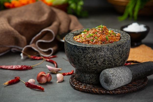 Ong pasta de chile en un mortero decorado con hermosas guarniciones.