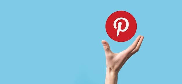 Onok, ucrania - julio 14,2021: empresario tiene, clics, icono de pinterest en sus manos. red social. red global y conexión de cliente de datos. red internacional.