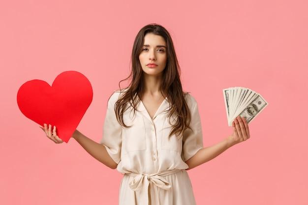 Opciones, estilo de vida y concepto de relación. mujer joven atractiva y atractiva de aspecto serio que te hace decidir, qué es el amor o la riqueza importante, tener grandes dólares en efectivo y un corazón de tarjeta de san valentín