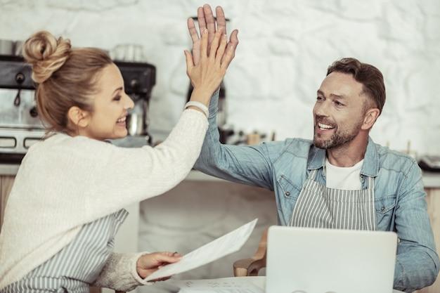 Operación exitosa. sonriente hombre de negocios dando un choca esos cinco a su bella pareja después de una productiva jornada de trabajo.