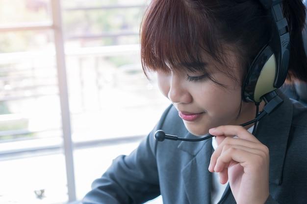 Operador amistoso de la mujer joven asiática o agente del centro de atención telefónica con los auriculares que trabajan en el centro de atención telefónica