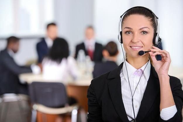 Operador de atención al cliente femenino con auriculares y sonriendo.