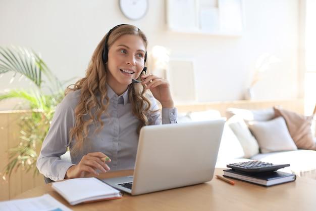 Operador autónomo hablando con auriculares y consultando a clientes desde casa.