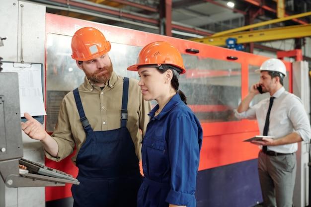 Operador barbudo en casco enseñando a aprendiz asiático a usar la máquina cnc en la tienda de la fábrica moderna