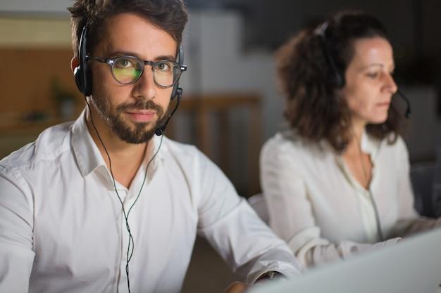 Operador de call center guapo en anteojos mirando a cámara