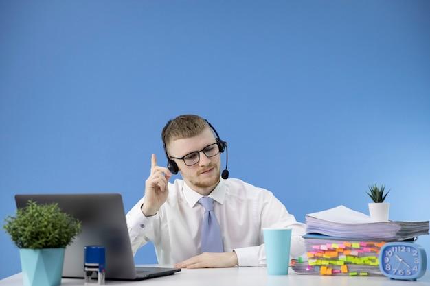 El operador de call center masculino en auriculares consulta al cliente en línea en una oficina moderna