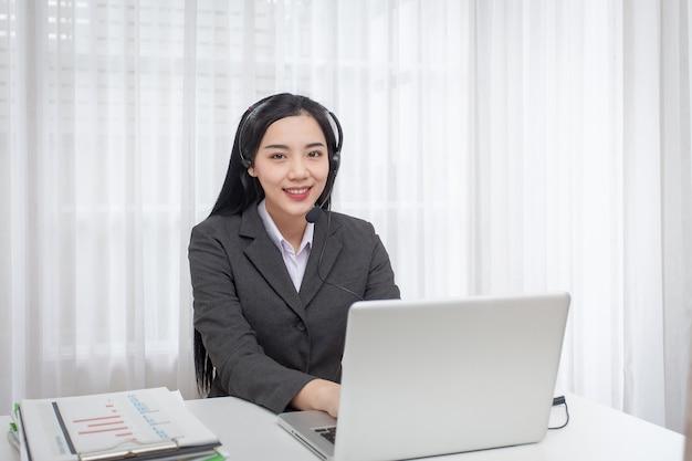 Operador de centro de llamada de mujer joven que trabaja en la oficina. consultor de escritorio de servicio hablando.