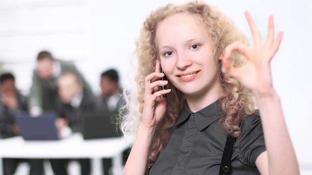 Operador de centro de llamadas hermosa joven hablando por teléfono celular con el equipo en el fondo