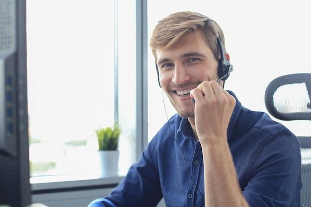 Operador de centro de llamadas masculino joven hermoso amistoso sonriente.