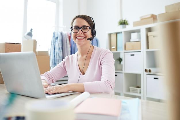 Operador exitoso mirándolo mientras consulta a clientes en línea