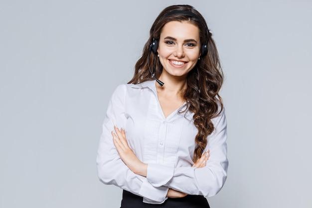 Operador joven agente mujer con auriculares de pie cerca de gris. servicio de call center.