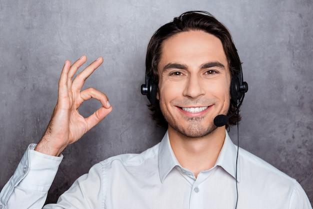 Operador joven guapo en call-center con auriculares mostrando ok