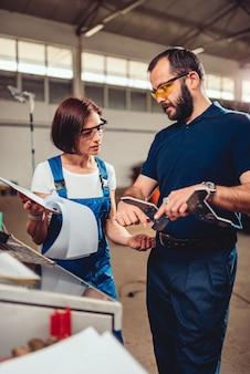 Operador de máquina cnc femenino y supervisor que mide el producto cortado