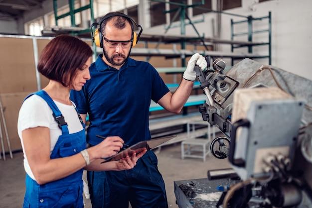 El operador de la máquina de corte de sierra de cinta toma con el supervisor de fábrica