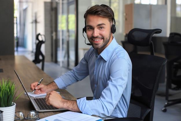 Operador masculino alegre del teléfono de la ayuda joven en el auricular, en el lugar de trabajo mientras usa la computadora portátil, el servicio de ayuda y el concepto del centro de llamadas de la consulta del cliente.