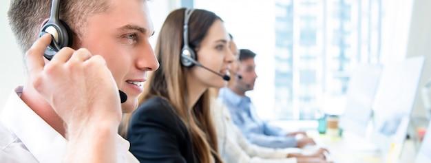 Operador masculino con equipo de trabajo en call center.