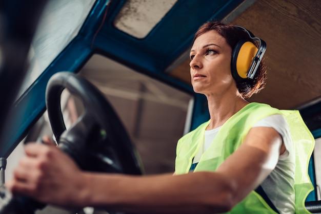 Operador de montacargas mujer conduciendo vehículo