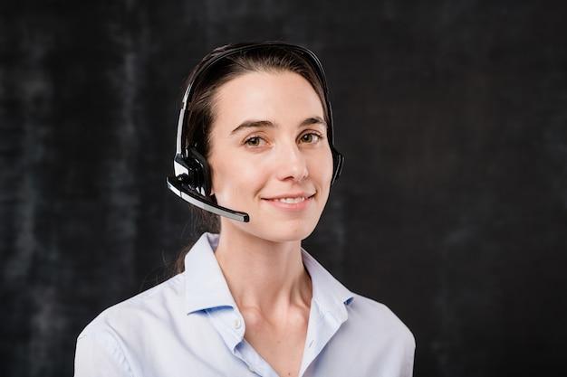 Operador morena bastante joven con auriculares hablando con los clientes durante el trabajo frente a la cámara contra el fondo negro