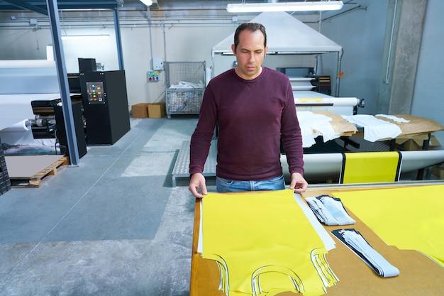 Operador de producción hombre en la fábrica de moda de transferencia