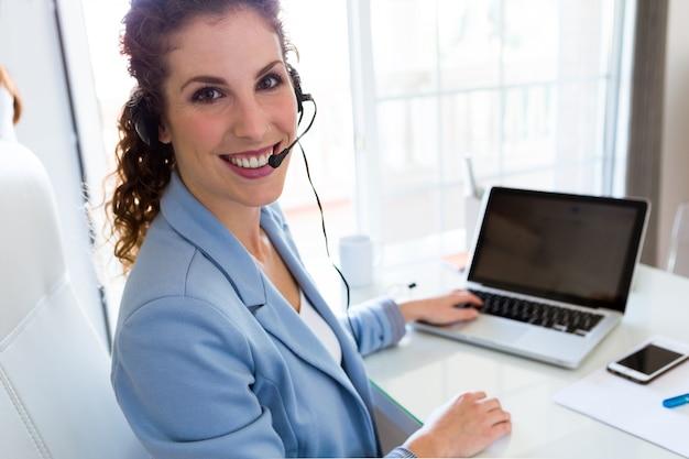 Operador de servicio al cliente hablando por teléfono en la oficina.