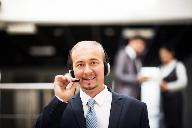 Operador de servicio al cliente que trabaja en el centro de llamadas de servicio de asistencia y consultoría de oficina