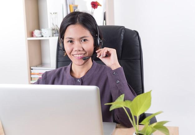 Operador sonriente feliz de la atención al cliente de las mujeres de asia con las auriculares en oficina de escritorio.