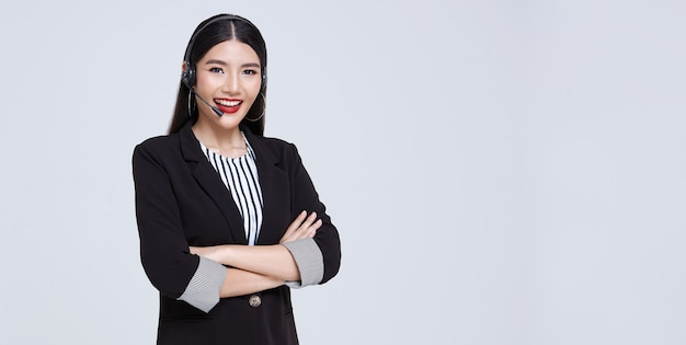 Operador de teléfono de soporte al cliente de empresaria asiática sonriente aislado sobre fondo gris. centro de llamadas y concepto de servicio al cliente.