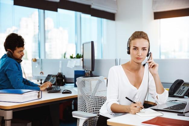 Operador de teléfono de soporte femenino hermoso joven hablando, consultoría, sobre oficina