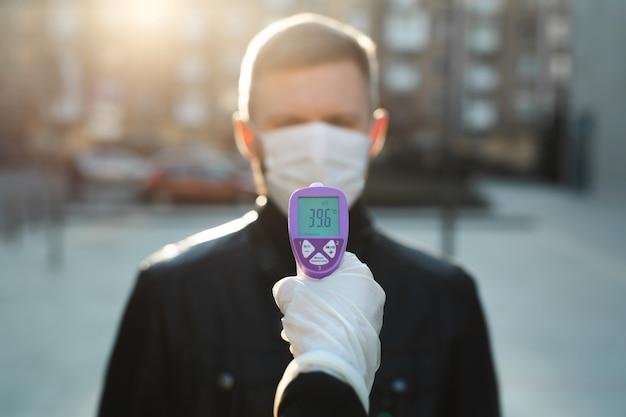 El operador verifica la fiebre con un visitante del termómetro digital en el mostrador de información para escanear y proteger contra el coronavirus covid-19