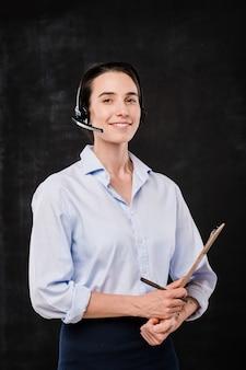 Operadora joven alegre con portapapeles organizando el trabajo mientras habla con los clientes sobre fondo negro
