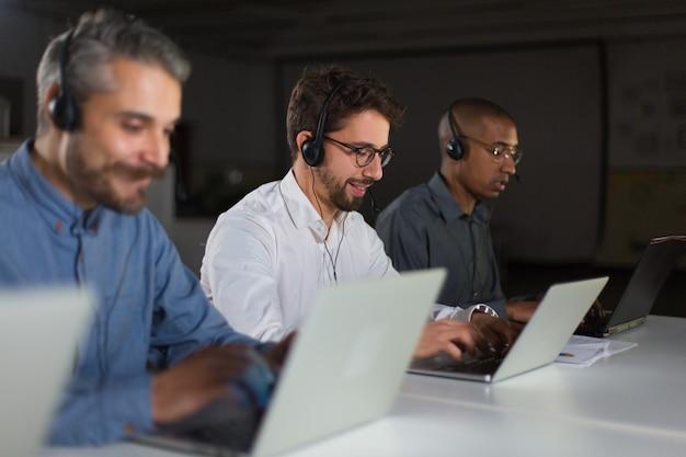 Operadores de call center alegres durante el proceso de trabajo