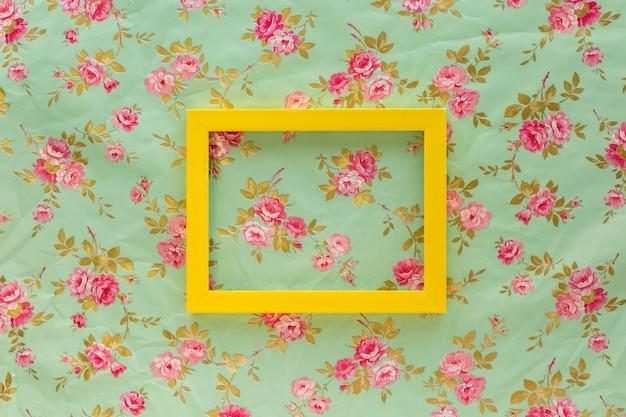 Opinión de alto ángulo del bastidor vacío amarillo contra fondo del estampado de flores