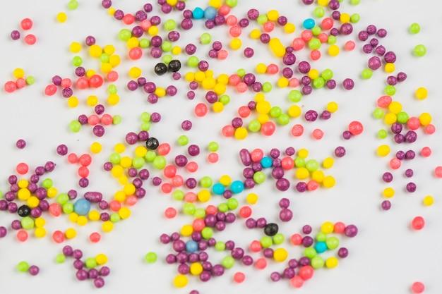 Opinión de alto ángulo de las bolas dulces coloridas del azúcar en el fondo blanco
