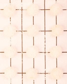 Opinión de alto ángulo del chocolate hecho en casa del coco dispuesto en una fila sobre el mantel a cuadros blanco