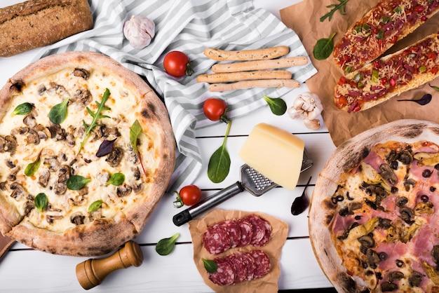 Opinión de alto ángulo de la comida italiana fresca deliciosa en el mantel sobre la tabla blanca