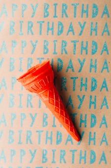 Opinión de alto ángulo del cono de helado vacío en el papel del regalo del feliz cumpleaños