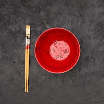 Opinión de alto ángulo del cuenco chino vacío y de palillos de madera sobre fondo negro texturizado