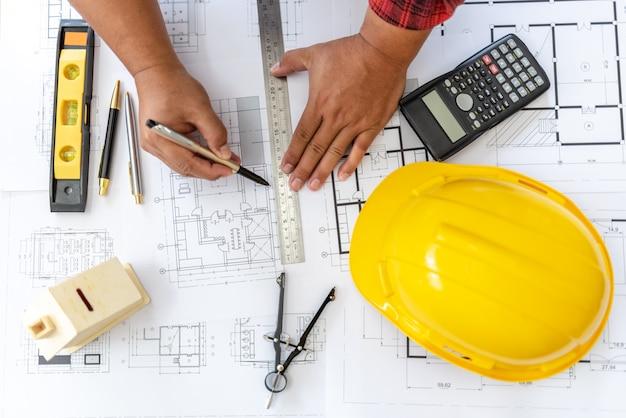 Opinión de alto ángulo del ingeniero asian person drawing architect plan en la tabla sobrepeso.
