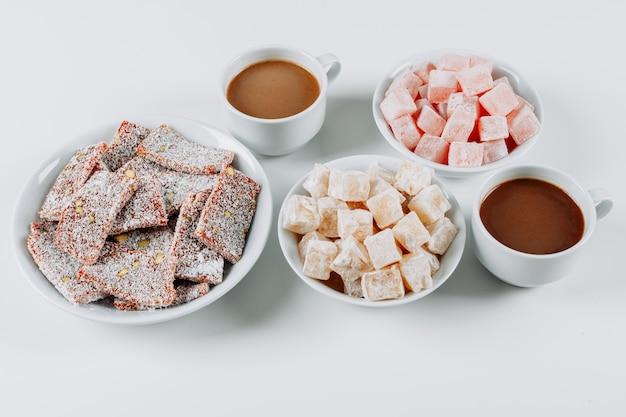 Opinión de alto ángulo lokums del placer turco en cuencos, con café en el fondo blanco. horizontal