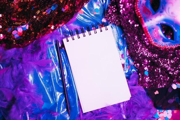 Opinión de alto ángulo de la máscara y de apoyos elegantes del carnaval con la libreta en blanco; bolígrafo