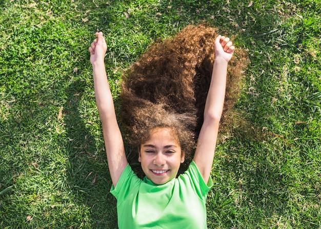 Opinión de alto ángulo una muchacha feliz que miente en hierba en parque
