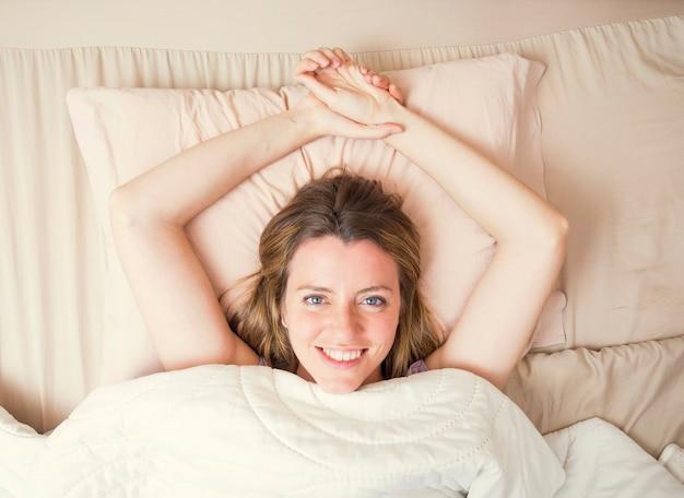 Opinión de alto ángulo la mujer joven sonriente que miente en la cama que mira para arriba