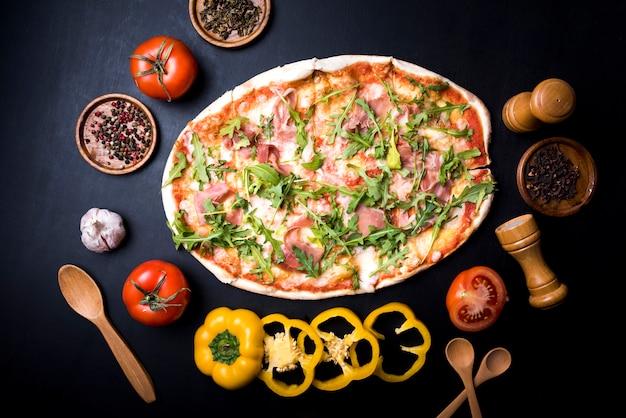 Opinión de alto ángulo de la pizza sabrosa fresca rodeada con los vehículos; especias y hierbas sobre el mostrador de la cocina