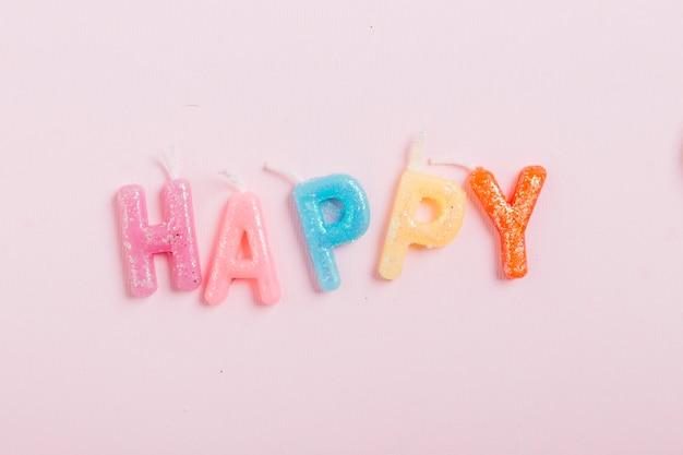Opinión de alto ángulo de las velas felices de la palabra en fondo rosado